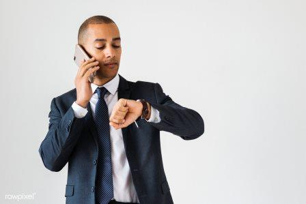Businessman talking on call checking time fro wrist watch