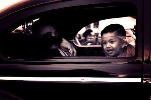 A child inside a vehicle with a parent