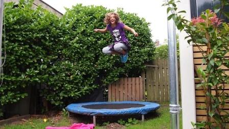 kids enjoying trampoline jump at the backyard